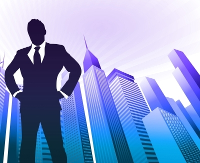 Image of business man figure prominently standing in front of skyline.